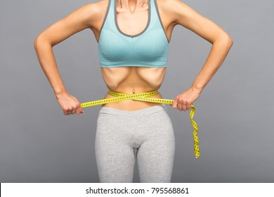 Dieting, anorexia. Thin woman showing her narrow waist using measure tape.