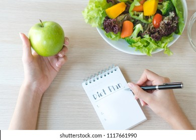 Dieting and calorie control for wellness. Woman calculate calories of food in breakfast during dieting for lose weight program and take notes.