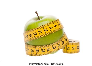 Dieting concept Green apple with measuring tape on white background