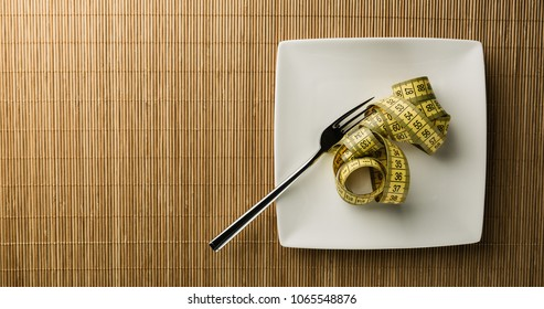 Dieting concept - measuring tape curled up on a white dining plate with a fork.
