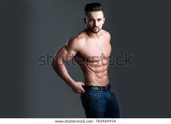 Dieting and fitness. Athletic bodybuilder man on grey background. Coach sportsman with bare chest in jeans. Sport and workout. Man with muscular body and torso.