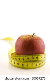 Dieting and health. A crunchy red apple surrounded by a yellow measuring tape