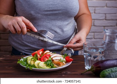 Dieting, healthy low calorie food, weight losing concept. Overweight woman with measuring tape on her waist eating salad from a bowl
