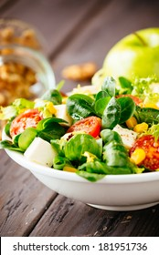 Dieting healthy salad on rustic wooden table. Mixed greens, tomatos, diet cheese, olive oil and spices for healthy lifestyle concept.