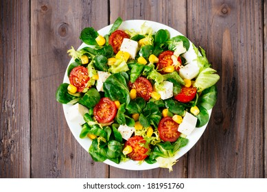 Dieting healthy salad  on rustic wooden table top view. Mixed greens, tomatos, diet cheese, olive oil and spices for healthy lifestyle concept.