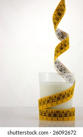 Dieting on low fat food (milk). A glass of low fat milk, surrounded by a coloured measuring tape, hanging  from above
