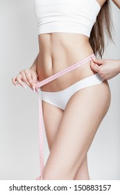 Dieting. Professionaly retouched studio HD capture of a beautiful young woman measuring waist