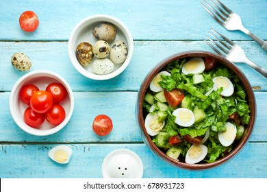 Dieting salad with lettuce, cherry tomatoes, cucumber and quail eggs on blue table with ingredients top view