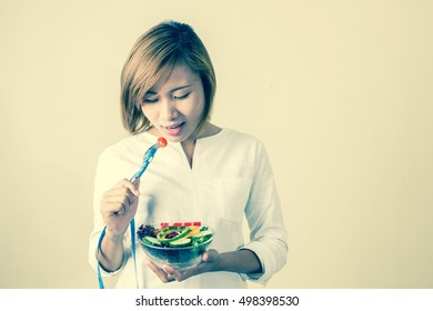 Dieting weight loss concept. young woman holding fork with fresh mixed vegetables and measuring tape on white background