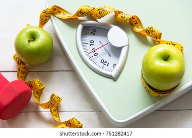 Dietitian lifestyle use Green apple prevention fat with weight scale and measuring tape for the healthy diet exercise slimming diabetes. top view,  Diet and Healthy Concept