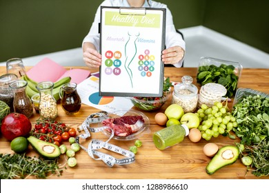 Dietitian showing a scheme with vitamins and minerals sitting at the table fulll of variuos healthy products indoors. Healthy eating concept