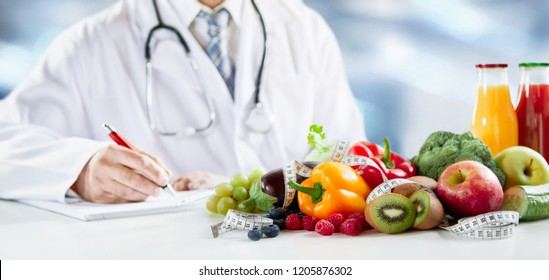 Dietitian writing a prescription for a healthy diet with assorted fresh fruit and vegetables in the foreground