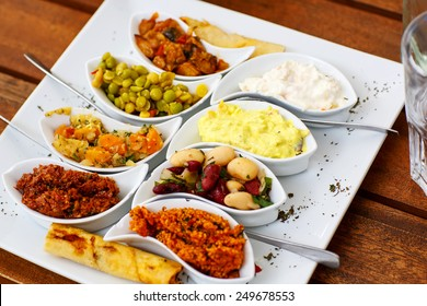 Differen appetizer and anti pasti on white plate in cafe or restaurant