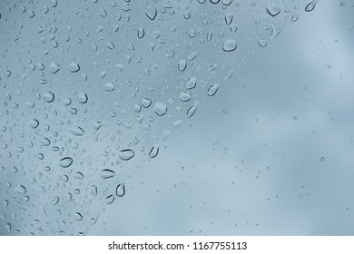 Difference size of raindrops on glass window of car with cloudy sky in the background