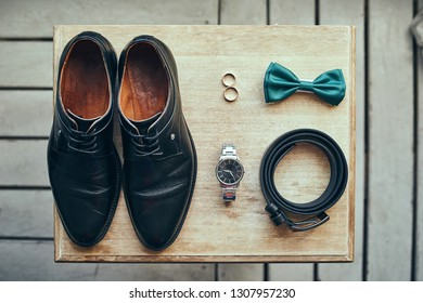 different accessories of a businessman for creating a style of a people lie on a wooden background