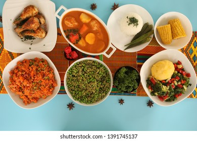 Different African Food on Top of the Table Consisting Jollof Rice, Chicken Stew,Spinach Rice,White Rice and Ugali