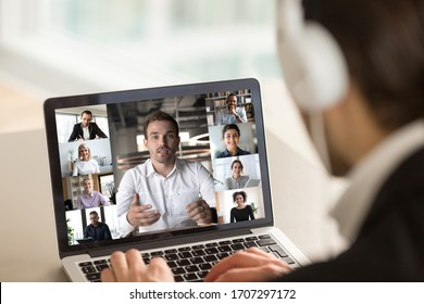 Different age and ethnicity diverse businesspeople participating at group videocall, laptop screen webcam view over man in headphones shoulder. Distant communication videoconference activity concept