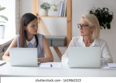 Different ages women colleagues 50s and young female workmates sit at office desk looking with enmity at each other. Negative attitude, conflict at workplace, misunderstanding generational gap concept