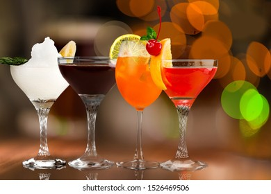 different alcohol cocktail drinks with fruit flavors , served in a fancy bar          - Image