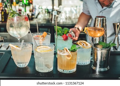 Different alcoholic cocktails on bar table, summer cocktails made by bartender