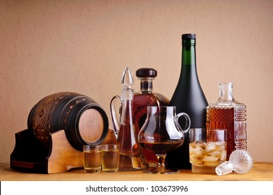 different alcoholic drinks, brandy, cognac and whiskey on a wooden background