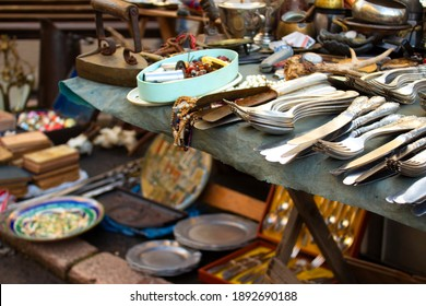 Different antiques on flea market or festival - aged vintage silver cultery - spoons, knifes, forks, and other vintage things. Collectibles memorabilia and garage sale concept, selective focus