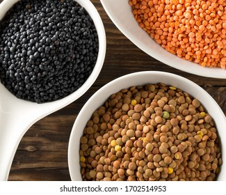 Different assorted lentils mix with red, brown and black beluga lentils in white bowls on brown wooden table background top view flat lay from above - selective focus