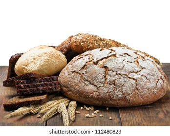 different assortment fresh bread and wheat ears on the wooden table