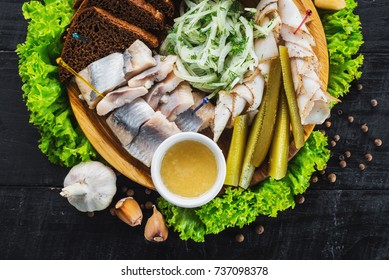 Different assorts of fish, meat and vegetables on black wooden board