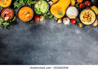 Different autumn soups set. Assortment vegetable soups in portion bowls - corn, potato, pumpkin, tomato, zucchini, broccoli cream soups. On black concrete background top view copy space