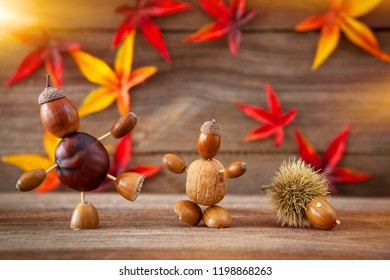different autumn tinker figures made with chestnuts,acorns and calybium on wooden background
