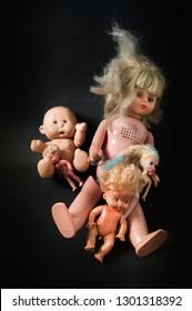 different baby dolls on black background
