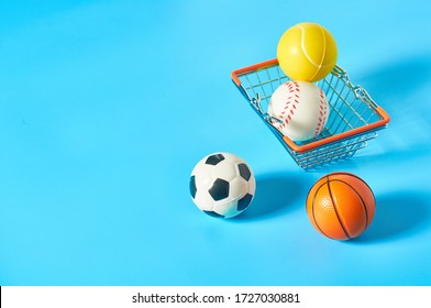 Different balls in metal market basket on blue background. Purchasing sport accessories. Concept of corruption in sport