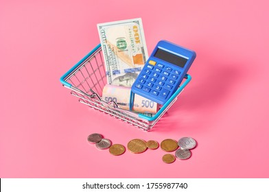 Different banknotes, coins and blue calculator in metal market basket on pink background. Buy or sale money. Currency exchange concept