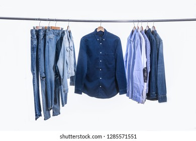 Different blue jean shirts and jacket, blue jeans are hanging on metal hangers.