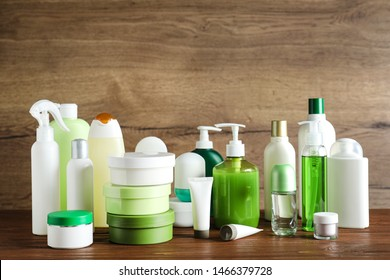 Different body care products on table against wooden background