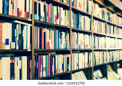 Different books on shelves in library