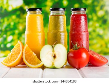 different bottles of juice with fruits on wooden table