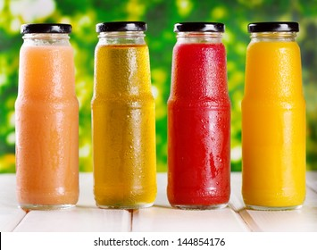 different bottles of juice on wooden table