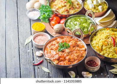Different bowls with assorted indian food on dark wooden background. Dishes and appetizers of indian cuisine. Chicken, curry rice, lentils, paneer, chapati and spices.