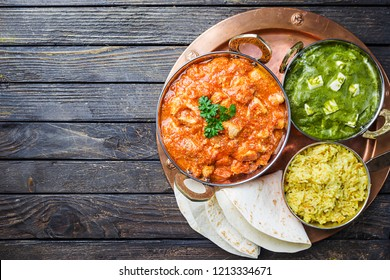 Different bowls with assorted indian food on dark wooden background, top view. Dishes and appetizers of indian cuisine. Chicken, curry rice, lentils, paneer, chapati and spices.