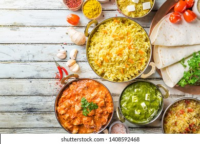 Different bowls with assorted indian food on white wooden background, top view. Dishes and appetizers of indian cuisine. Chicken, curry rice, lentils, paneer, chapati and spices.