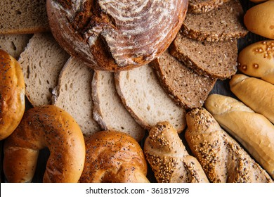 Different bread and bread slices, pastries combination, rye bread with grains, food background.