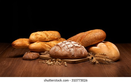 Different bread and wheat on dark wooden table background