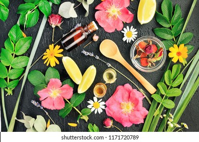 Different bright natural herbal ingredients, leaves flowers citrus fruit & essential oil bottle for organic skincare treatment above black table. Handmade botanical healing cosmetics.