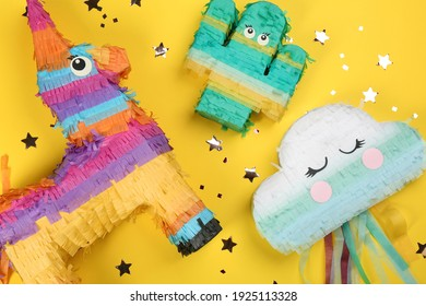 Different bright pinatas on yellow background, flat lay