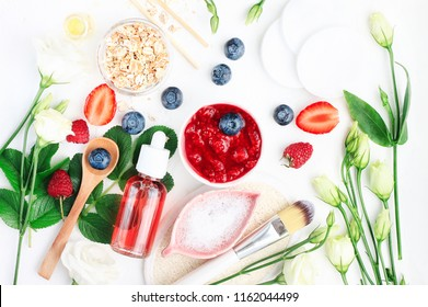 Different bright set skin care beauty products above on white table, ingredients prepared for making cosmetics. Face mask and tonic homemade from fresh berries,  herbal leaves, rolled oat flakes.
