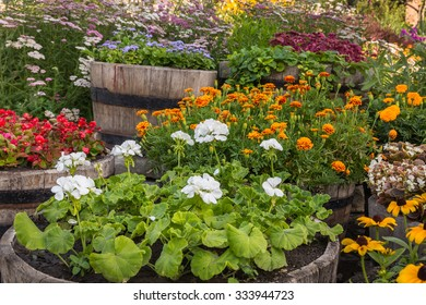 Different bright summer flowers in a wooden barrels