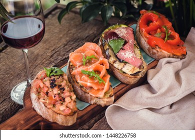 different bruschetta on a wooden board with a glass of wine
