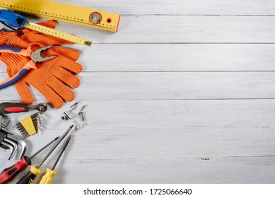 Different building or crafting tools and gloves flatlay on white wooden background